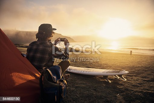 Shot of a surfer by his tent while waiting for the perfect wave