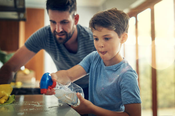 Take that germs! Shot of a father and son cleaning the kitchen counter together at home chores stock pictures, royalty-free photos & images