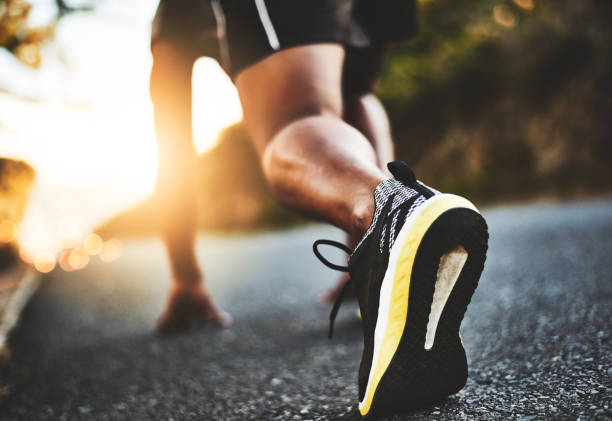 Take that step towards a healthier you Low angle shot of a man out exercising on a tarmac road track starting block stock pictures, royalty-free photos & images