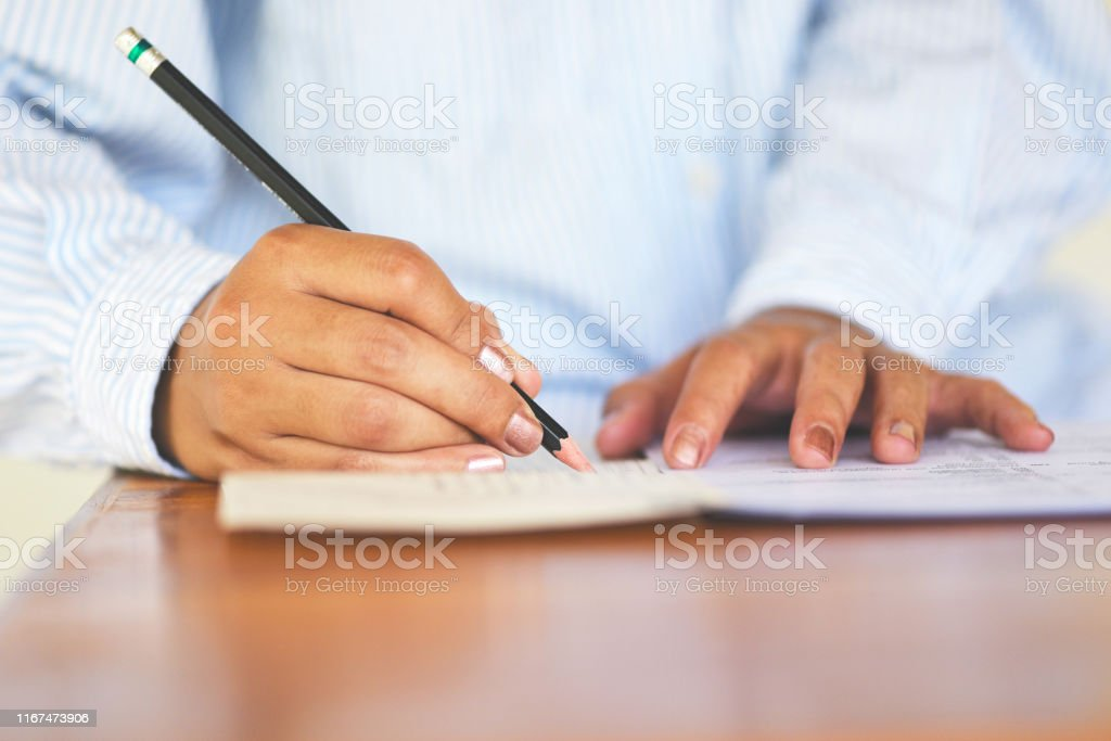 take the exam final high school university student holding pencil...