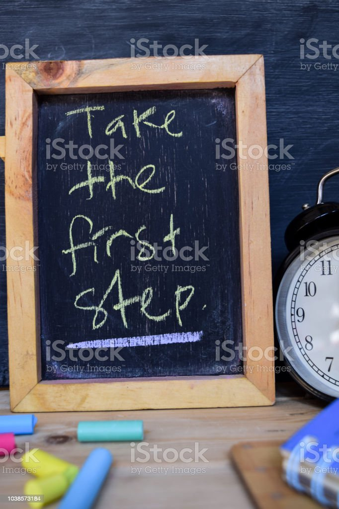 Take the first step. Back to school concept. Alarm clock on wooden...