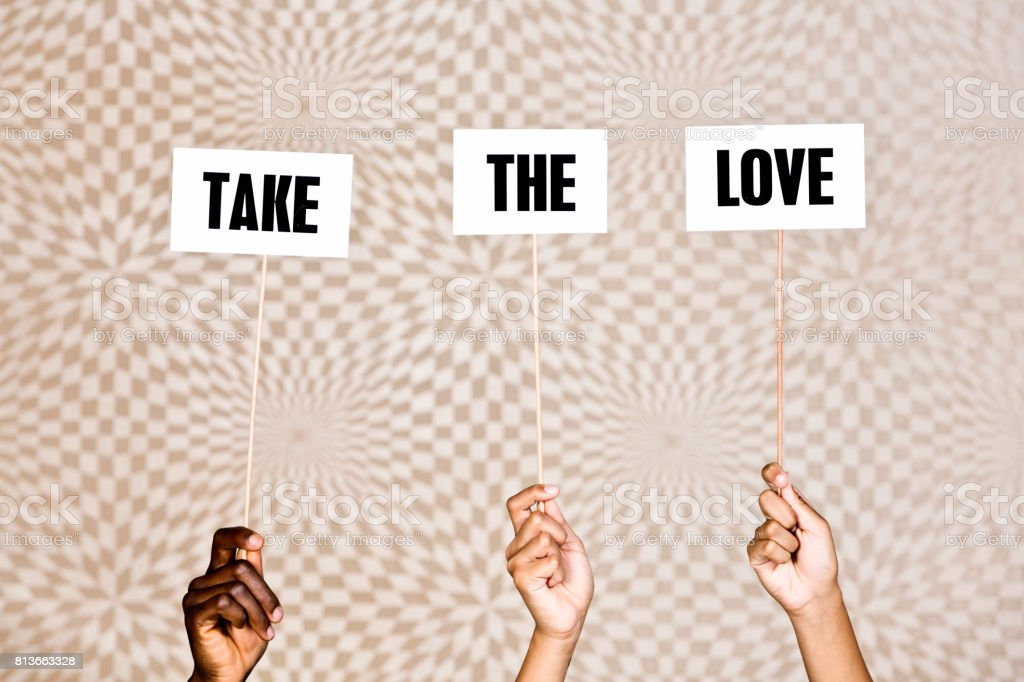'Take the love' say hand-held signs on  psychedelic background stock photo