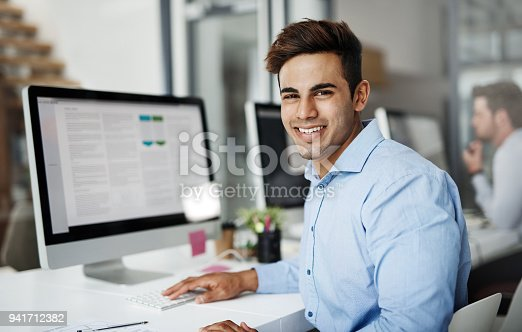 Portrait of a handsome young businessman using a computer in a modern office