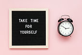 istock Take time for yourself. Motivational quote on letterboard and black alarm clock on pink background. Top view Flat lay Copy space Concept inspirational quote of the day 1180975850