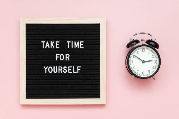 花點時間給自己。在粉紅色背景的信板上和黑色鬧鐘上引用激勵性報價。頂視圖 平面 佈局 複製 空間 概念鼓舞人心的報價的一天 - 鬆弛 個照片及圖片檔