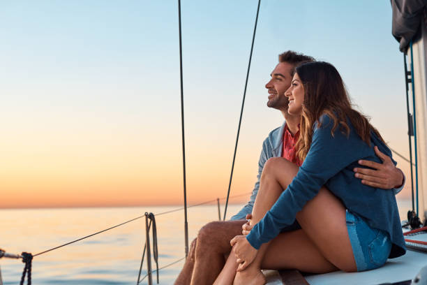 Take to the seas for a life of ease Shot of a young couple enjoying a cruise out on the ocean romantic activity stock pictures, royalty-free photos & images