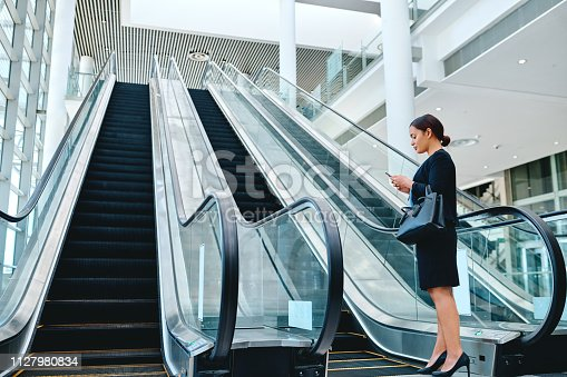 Low angle shot of an attractive young businesswoman sending a text message while standing in the airport