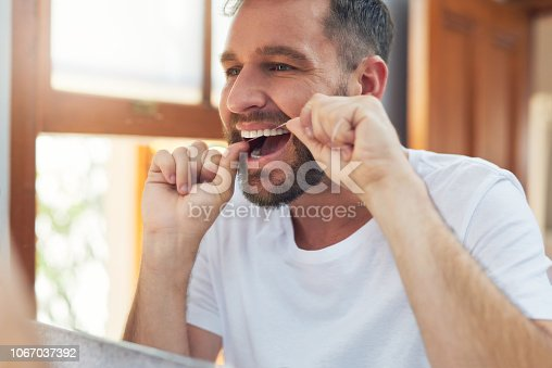Shot of a handsome young man flossing his teeth in the bathroom