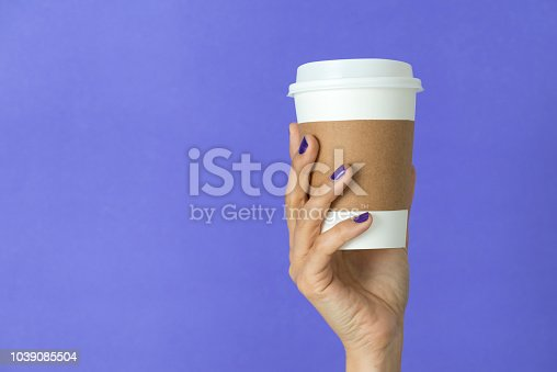 Paper cup of takeaway coffee in the hand.