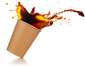coffee splashing out of a take-out cup tilted on white background