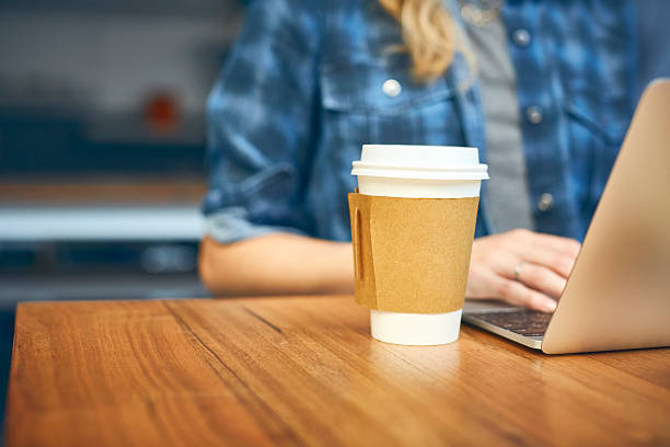 Takeaway coffee with woman on laptop in background stock photo