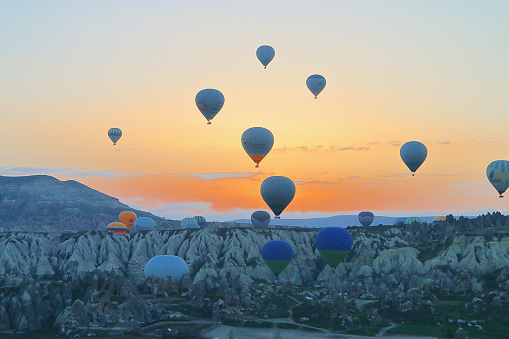The picture was taken in the area called Cappadocia in Turkey. The picture shows the rise of a large number of balloons at the dawn of the sun.