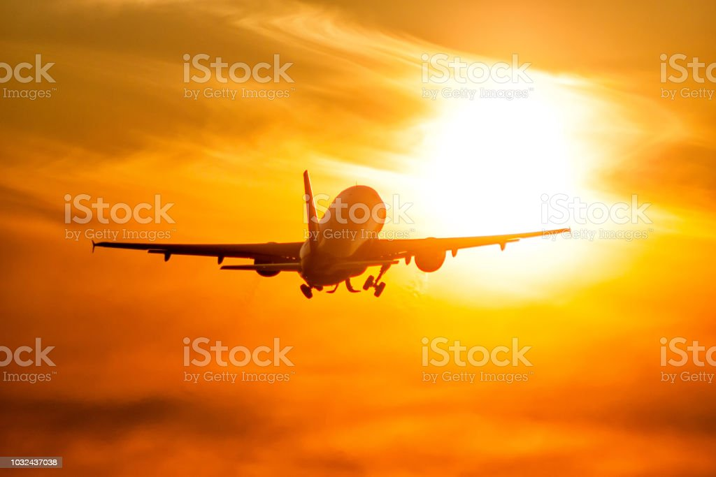 Take-off of a passenger airplane directly to the rising morning sun стоковое фото