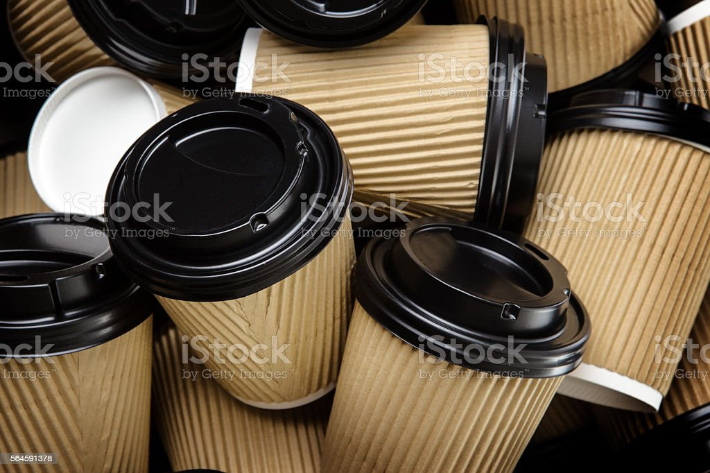 Pile of disposable take away coffee/ tea cups with black lids