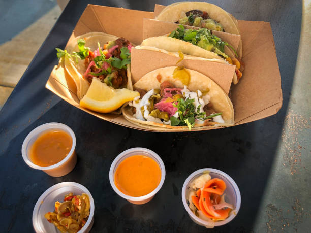 Takeout Containers of Vegan Tacos, Hot Sauces and Pickled Vegetables stock photo