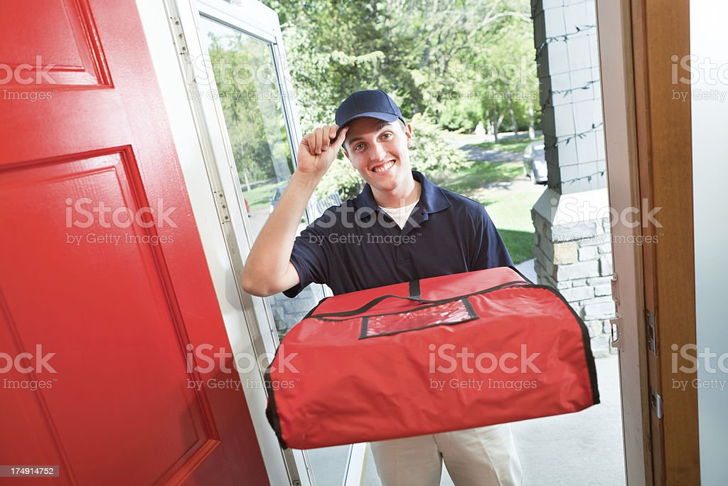 Take-out Pizza Delivery Man Arriving at Customer's Home Door stock photo