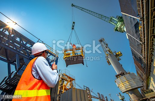 foreman, supervisor, worker, loading master in works at job site, control to the teamwork by walkie talkie radio for job done in the same direction, working at risk and high level of insurance