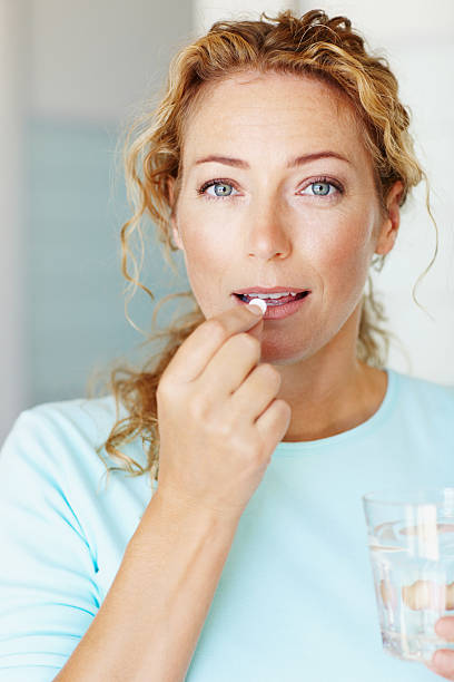 Taking a boost for her health - Vitamins & Supplements A mature woman taking a vitamin supplement with a glass of water woman taking pills stock pictures, royalty-free photos & images