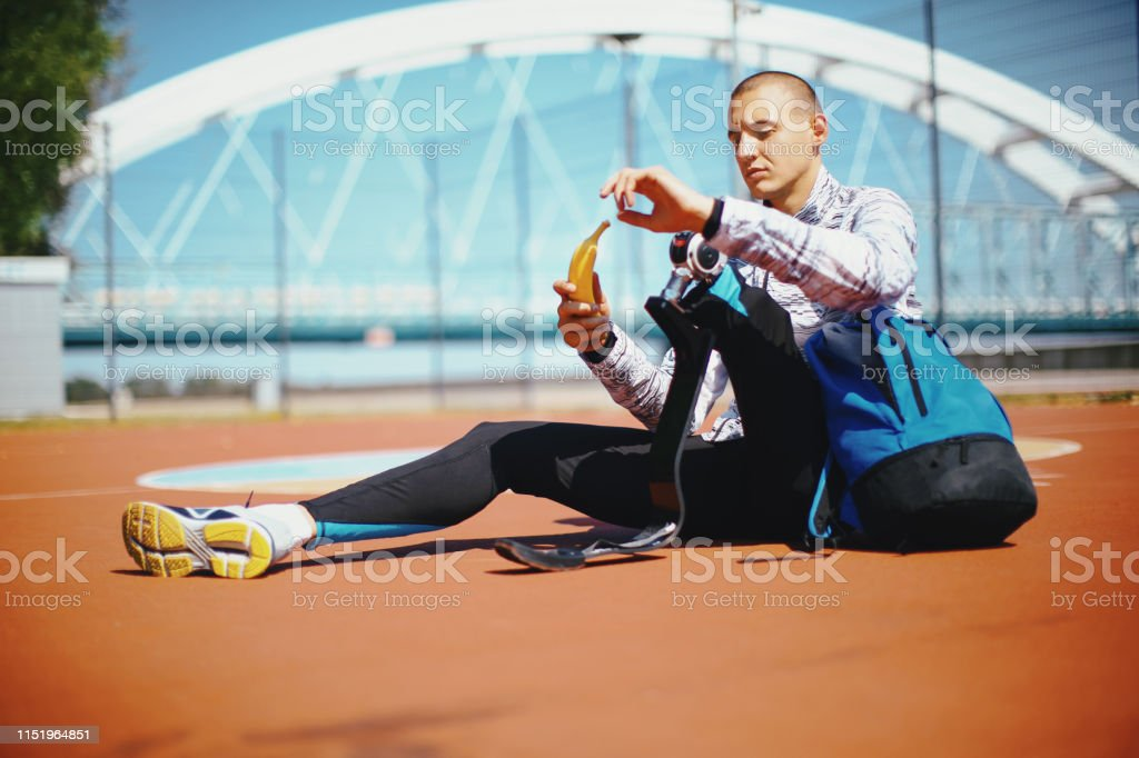Young male athlete with artificial leg taking a break at stadium...