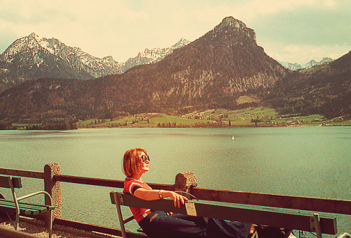 Vintage imageof a woman taking a break on a banch at the Alps