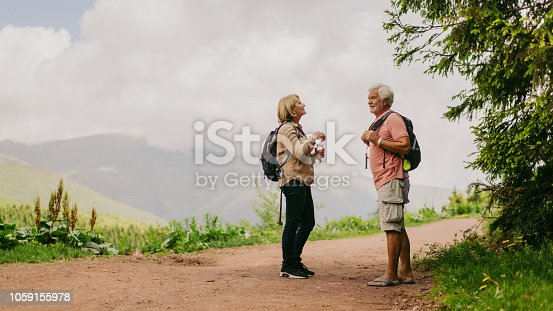 Photo of an elderly couple taking a break during their hike with backpacks // wide photo dimensions