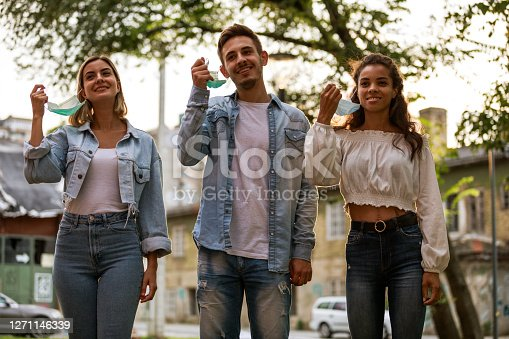 Three cheerful friends taking a break from wearing protective face masks by removing them during a relaxing walk they are taking together on the city street.