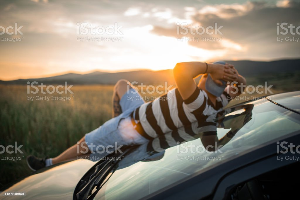 Young man with sunglasses and cap on a road trip on country side road...