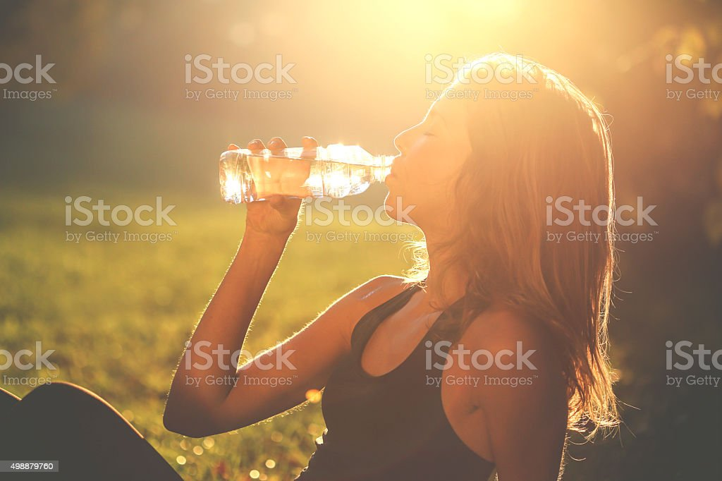 Woman drinking from a water bottle at sunset. About 20 years old...