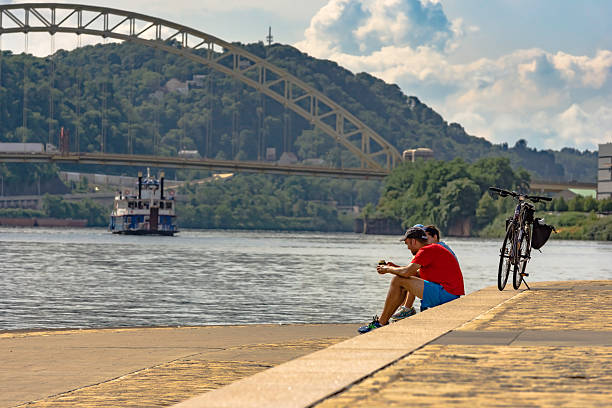 Taking a Break Pittsburgh, Pennsylvania, United States - July 30, 2016: Two bikers take a break next to the Ohio River at Point State Park with a riverboat and Fort Pitt Bridge in the background pittsburgh bridge stock pictures, royalty-free photos & images