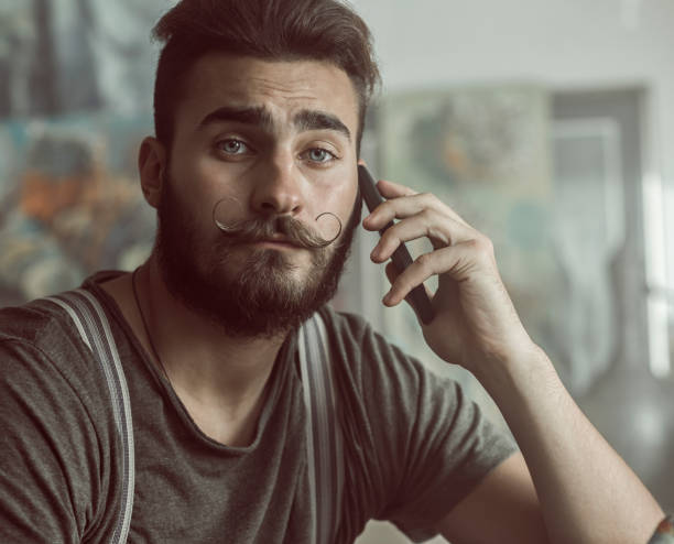 Taking a break Young artist talking on a mobile phone in an atelier. mustache stock pictures, royalty-free photos & images