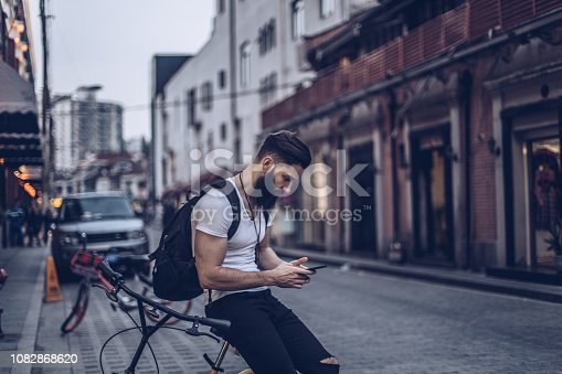 Young handsome man sitting on bicycle outdoors and texting