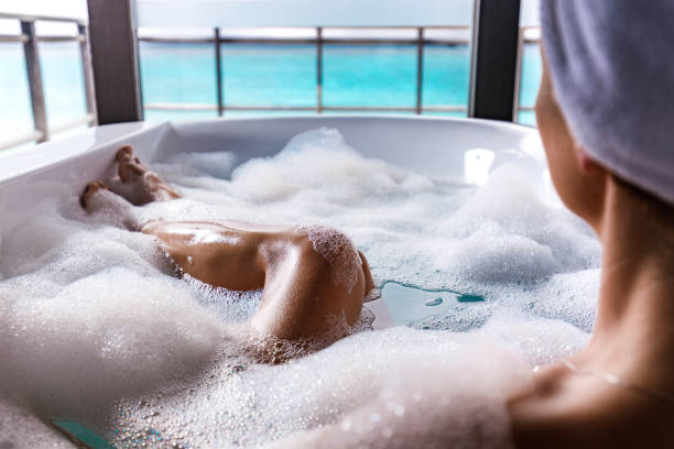 Taking a bubble bath! Unrecognizable woman pampering while relaxing in a bathtub full of soap sud. bubble bath stock pictures, royalty-free photos & images