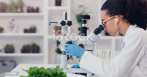 Shot of a young scientist using a microscope in a lab