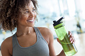 beautiful young woman holding a plastic bottle of water at the gym