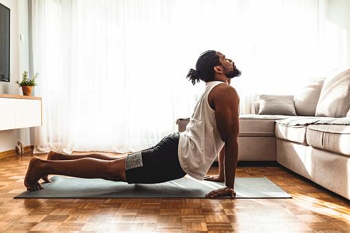 Indoor shot of handsome young man practicing yoga. Fitness man meditating with his eyes closed while doing cobra pose in living room.