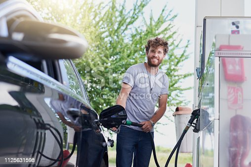 Cropped portrait of a handsome young man refuelling his car at a gas station