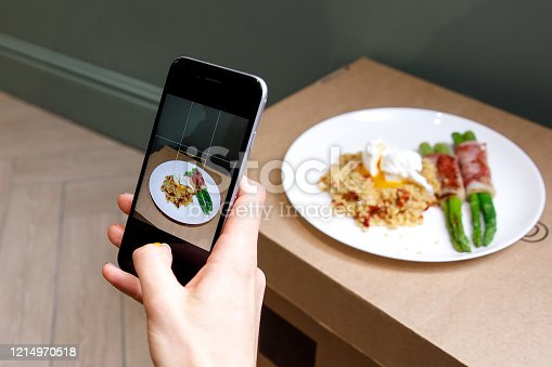 Taking a photo of porridge, vegetables, and bacon with a smartphone