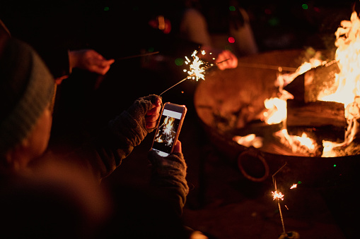 Woman is using her smart phone to take a photo of a sparkler she is holding by the bonfire.