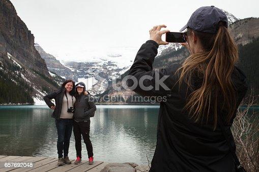 Woman with long hair taking photo of two women at Lake Louise, Alberta