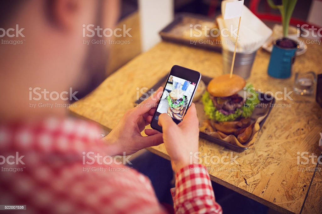 Taking a pic of food for social network site stock photo