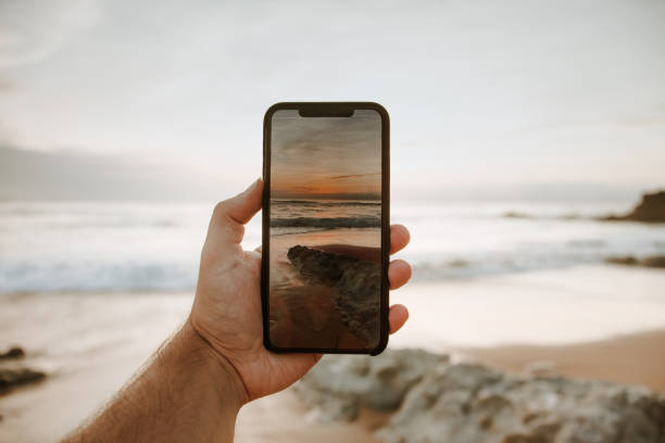 Taking a picture of a beautiful sunset by the sea with a smart phone stock photo