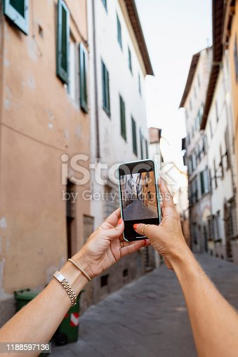A point of view shot of an unrecognisable caucasian woman taking a picture with her smart phone of an old Italian street.