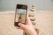Taking a picture of a balanced stack of stones at the beach with a smartphone
