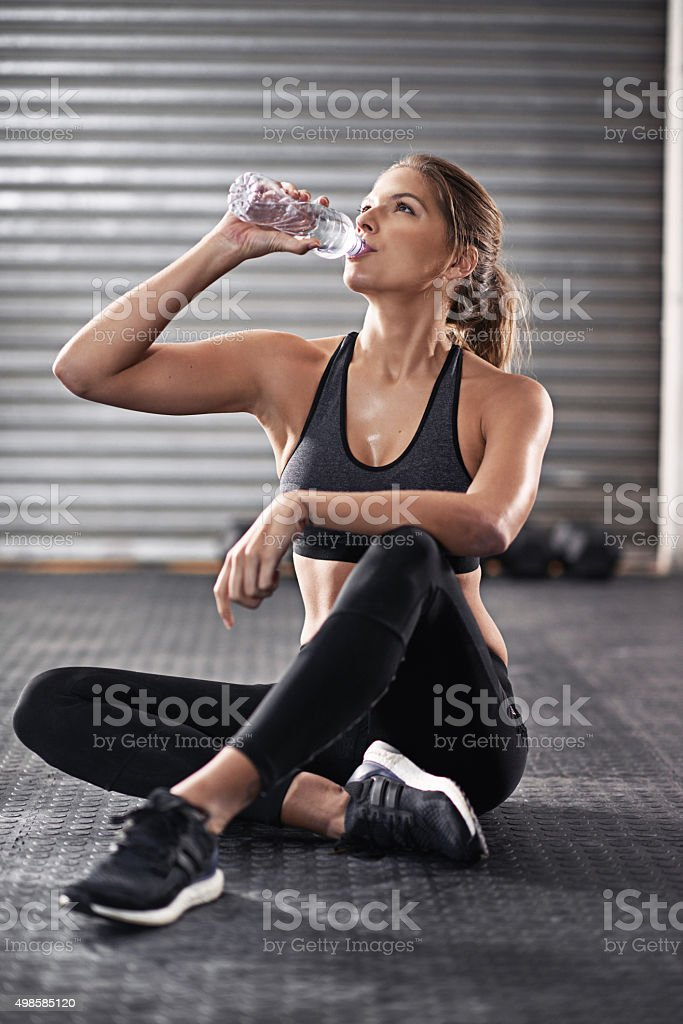 Cropped shot of a young woman drinking from her water bottle at the...
