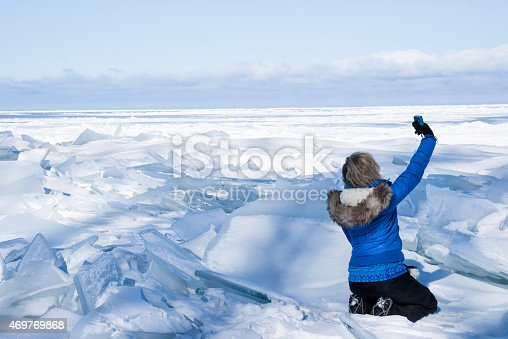 Blond woman sitting in jumbled ice on Lake Superior in winter takes a selfie with her phone, Apostle Island National Lakeshore, Cornucopia, Bayfield County, Wisconsin, USA