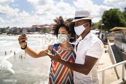 Young afro couple wearing face masks taking a photo in their vacation in time of Coronavirus pandemic