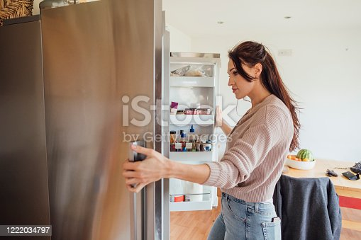 Woman looking into her fridge while taking a study break.