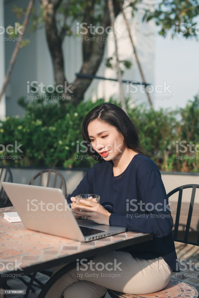 Taking advantages of free Wi-Fi. Beautiful young woman working on laptop and smiling while sitting outdoors stock photo