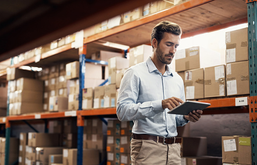 Shot of a young man using a digital tablet while working in a warehouse