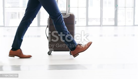 Cropped shot of an unrecognizable businessman walking and pulling a suitcase while in the office during the day